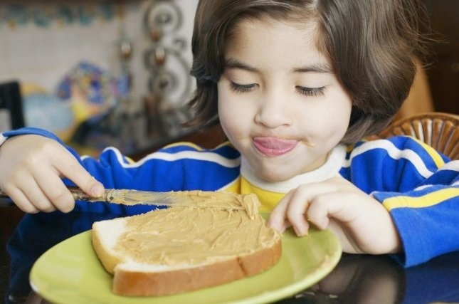 Boy eating a peanut butter sandwich