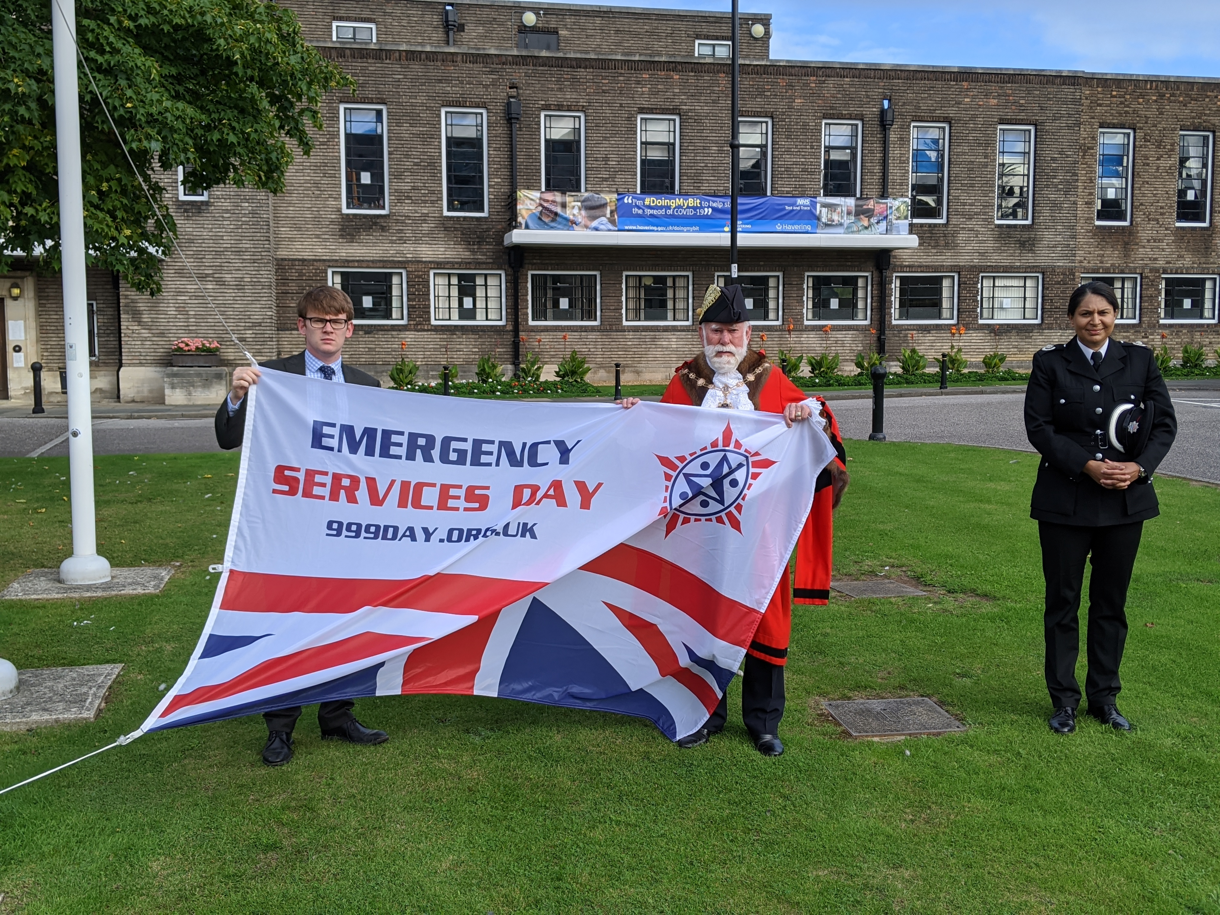 Councillor John Mylod, Mayor of Havering, Councillor Damian White, Leader of Havering Council, and Narinder Dail, Fire Borough Commander raise the flag to mark Emergency Services Day.