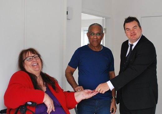 Mr and Mrs Colepil accepting the keys to their new home from Councillor Robert Benham, Deputy Leader of Havering Council
